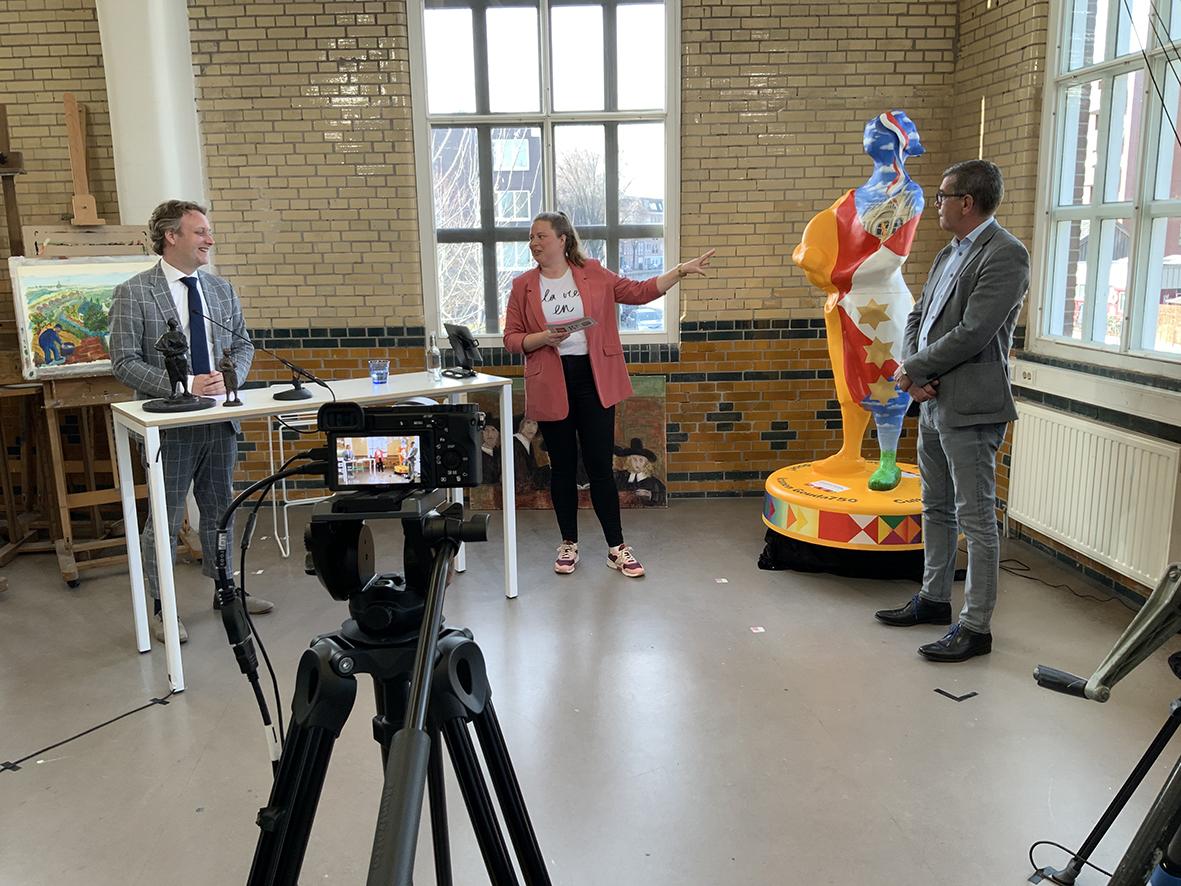 foto tijdens de livestream in de Garenspinnerij met het net onthulde icoon. Van links naar rechts op de foto: Pieter Verhoeve (burgemeester Gouda), Esther van Pomeren (presentator livestream) en Gerard van Nieuwpoort (Goudse Betonmortel Centrale).